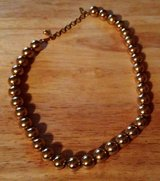 Gold colored ball necklace in Fort Polk, Louisiana