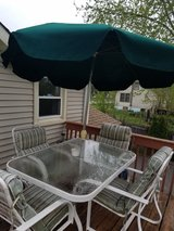 Green and white patio set with four chairs and umbrella in Aurora, Illinois