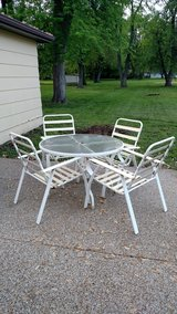 Older patio table and chairs with cushions in Belleville, Illinois