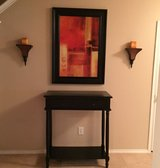 Black console table with art work, wall sconces in Tomball, Texas