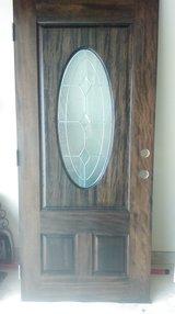 Solid wood with oval glass insert entry door in Conroe, Texas