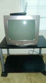 Small box tv with remote and entertainment center in Fort Lee, Virginia