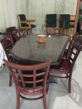 Large wood table with black Formica top and chairs in Joliet, Illinois