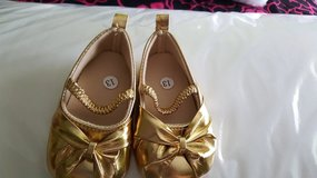 Gold bows infant shoes in New Lenox, Illinois
