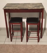 Bar table with two leather and wood stools in Ramstein, Germany