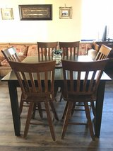 Heavy duty, solid wood dining table with 6 swivel chairs plus extension leaf. in Travis AFB, California