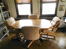 Light brown wood table and 4 swivel beige suede/ leather captain chairs in Glendale Heights, Illinois