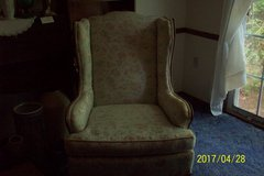 Wing back chair with muted floral fabric and wood trim in Goldsboro, North Carolina