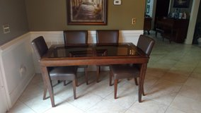 5x3 feet glass top wood dining room table 2 1/2 feet tall with 4 faux leather chairs in Warner Robins, Georgia