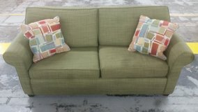 Green couch with abstract throw pillows in Camp Lejeune, North Carolina