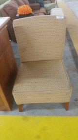 Tan armless accent chair in Camp Lejeune, North Carolina