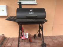 Charcoal Grill with cooking tools, bag of charcoal, and lighter fluid in Ramstein, Germany