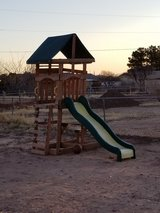 Outdoor playground with playhouse, slide, clumbing wall, table and bench, sand pit area in Alamogordo, New Mexico