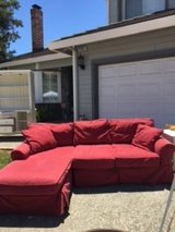 Red chaise model couch in Travis AFB, California