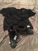 Youth football jersey and cleats in Fort Leonard Wood, Missouri
