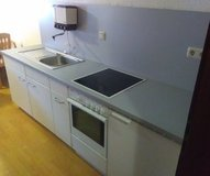 Small Ktichen with Cabinets, Stove, Refrigerater, Sink and grey wall panels. in Ramstein, Germany