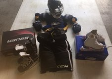 Lot of boys hockey equipment, gloves, helmet, shoulder pads and ice skates in Naperville, Illinois