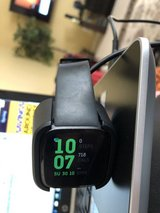 Fitbit Versa and battery charger in The Woodlands, Texas