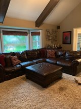 Brown leather sectional and ottoman in Chicago, Illinois