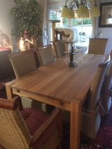 Oak dining table with 8 wicker chairs in Ramstein, Germany