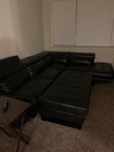 Black leather sectional and ottoman in CyFair, Texas