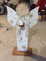Wooden angel with lighted candle in Oswego, Illinois