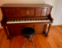 Player Piano, stool and cabinet with music rolls in Chicago, Illinois